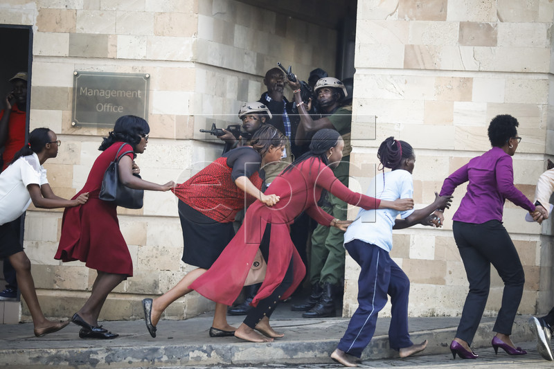 Women are evacuated out of the scene as security officers search for attackers during an ongoing gunfire and explosions in Nairobi, Kenya, 15 January 2019. According to reports, a large explosion and sustained gunfire sent workers fleeing for their lives at an upscale hotel and office complex in the Kenyan capital of Nairobi.  EPA-EFE/DAI KUROKAWA