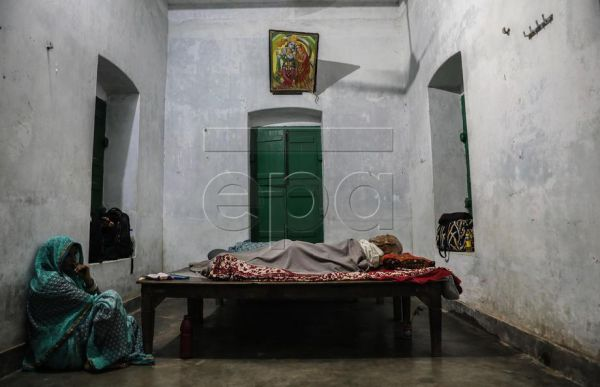 A relative sits next to the dead body of Kodu Singh Parmar, that died inside his room at Kashi Labh Mukti Bhawan in Varanasi, India, 09 October 2019. Kashi Labh Mukti Bhawan is a charity-run a place that offers lodging to those who wish to give up their last breath in the holy city of Varanasi (also known as Banaras or Kashi) to achieve Moksha, a Hindu term for enlightenment or release. There is a saying in Sanskrit, Kashyam Marnata Mukti, which means that one will get Moksha if he dies in Kashi. The city i