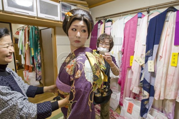 Twenty-year-old Ayana Takiguchi gets fitted into her kimono at a beauty shop on Coming of Age Day in Isumi city, Chiba province, Japan, 11 January 2010. The Coming of Age day is celebrated on the second Monday of January in Japan and is a national holiday. All young people who turn twenty years old this year celebrate in the day's ceremony. Age twenty is considered the beginning of adulthood and is the minimum legal age for voting, drinking, and smoking in Japan. For Takiguchi the day began at 3:30 a.m. in