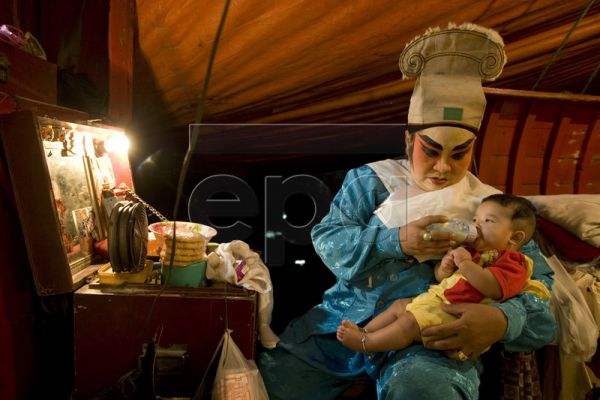Thai-Chinese singer of the Chinese Opera troupe, Suma Charasnaew, 54, feeds her colleague's baby during a performance at a Chinese Shrine in Thonburi district of Bangkok, Thailand, 06 February 2010. The troupe is not based at the shrine. They came here to perform 3 nights of shows as part of the upcoming Chinese Lunar New Year celebration. Chinese Opera is based on ancient tales of heroes and the supernatural. The 47-strong crew is a mix of Thai and Thai-Chinese as well as some illegal immigrants from China
