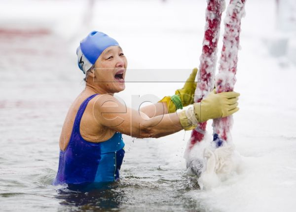 A file picture dated 07 January 2010 shows a woman reacting as she climbs out of a pool cut out of the frozen waters of the Songhua jiang river to entertain tourists who enjoy the performance as part of the International Harbin Ice and Snow Festival in Harbin, northern Heilongjiang province, China. This winter much of Europe and North America have experienced above average snowfall. Media reported that blizzards hit cities in the north-eastern US, as government offices had been forced to close for three day