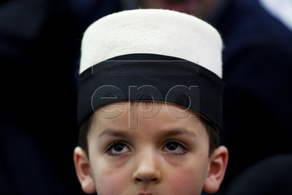 A young Kosovo dervish boy looks on during the celebration of Nowruz Day in the prayer room in the town of Rahovec, Kosovo, on 21 March 2010. Kosovar dervishes perform the same ritual every year to mark the Sultan Nowruz Day, which is the birthday of Imam Ali and the first day of Spring. In Kosovo, there are as many as 12 orders of this Sufi sect who trace their origins back to different saints and teachers but all unite in viewing Ali, nephew of the Prophet Muhammad, as their founder. The Kosovo Dervish co