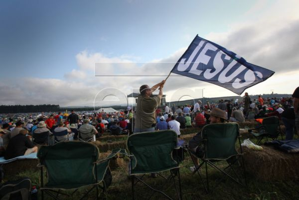 A man waves a flag reading 'Jesus' while waiting for a service with 300,000 Christian men at the Shalom farm during the annual Christian Mighty Men Conference, Greytown, South Africa, 18 April 2010. Six years ago, a Christian farmer named Angus Buchan invited a small group of men to Shalom, his farm located near Greytown in South Africa's Kwa-Zulu Natal province. The meeting, called 'Mighty Men,' was so popular that it grew into an annual event. From 16-18 April 2010, nearly 300,000 men of all races converg