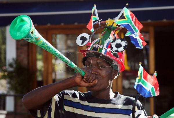 A street vendor blows a 'vuvuzela' trumpet and wears a South African 'makarapa' as he sells national flags at a street intersection in Johannesburg, South Africa, 05 May 2010. The Makarapa is a hand-cut and hand painted hard hat. The origin of the term 'Makarapa' goes back to the late 70's and early 80's. It's derived from Makarapa, meaning migrant worker. It's associated with the 'helmets' because they were used by migrant workers in the mines around Johannesburg. It belongs to the typical South African fo