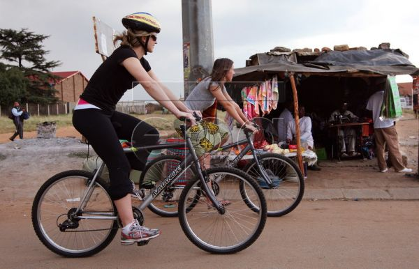 A group of American and European tourists ride past an informal tailor's shack during a bicycle tour through Soweto, South Africa, 19 March 2010. The tour starts at the Soweto Backpackers in Orlando West district where revered former President Nelson Mandela lived with his ex-wife Winnie Madikizela-Mandela before his nearly three decade imprisonment for resisting apartheid. It was also here that thousands of youths staged an uprising against the apartheid regime in 1976. The business owner Lebo Malepa is br