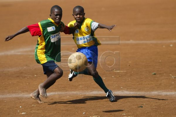 Eleven-year-old Erick Kipkuru of Sunrise (R) vies for the ball during his soccer match at a community field of Mathare slum, in Nairobi, Kenya, 22 May 2010. The soccer teams and tournaments are organized by Mathare Youth Sports Association (MYSA), a local non-government organization (NGO), that was initiated in 1987 in the aim of educating struggling youth of Mathare slum and promoting environmental improvement, HIV/AIDS prevention awareness, leadership training and community development through athletic ac