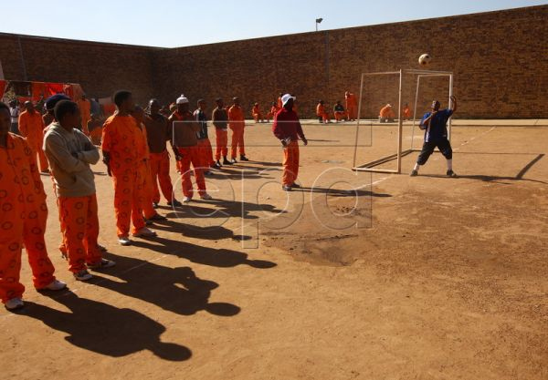 Inmates watch as the goalkeeper for a prison soccer team saves a shot at goal during a soccer match played in the dirt pitchat Boksburg prison, Johannesburg, South Africa, 03 June 2010. The prison will be marking the start of the FIFA 2010 Soccer World Cup by staging their own 'World Cup' for the inmates. Soccer is a way of life for the inmates who live for the game and most of the cells have their own team. The prison also invites soccer talent scouts to attend games with the hope of the scouts finding a t