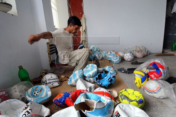 A worker with Anwar Khawaja Industries stitches soccer balls at a soccer ball factory in Sialkot, Pakistan, 08 June 2010. The soccer ball industry of Pakistan, principally concentrated in the city of Sialkot, has been under scrutiny in recent years for employing child workers. The Sialkot Chamber of Commerce and Industry has taken major steps towards elimination of child labor and the results have been encouraging. Soccer balls are made entirely by hand in Sialkot. They generally consist of a number of synt