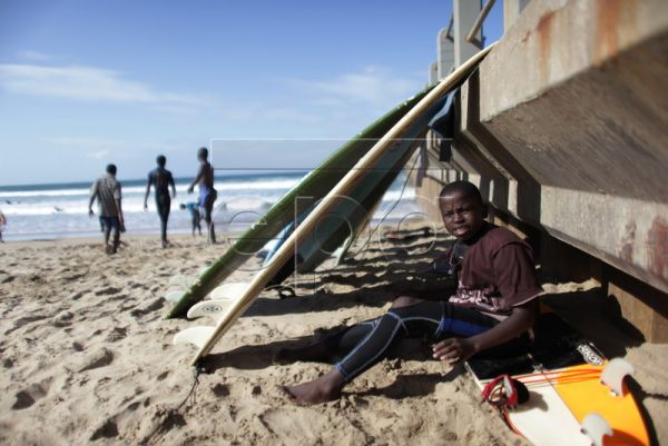 Surfing street child, Ntando Msibi, tries to warm up after a surf off New Pier in Durban, South Africa, 10 August 2010. The street children who surf are supported by the Umthombo street children organization. Umthombo is a unique South African street children organization led predominantly by former street children and aims to change the way that society perceives and treats street children. One of the treatment avenues is to teach the children to surf. In this way underprivileged children can enjoy a sport