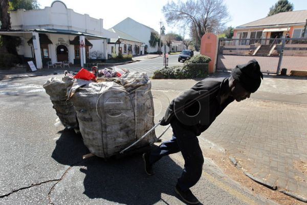 An unemployed man working as an informal recycler pulls a cart loaded with recyclable materials in Johannesburg, South Africa, 12 August 2010. Recycling for the average suburban household in South Africa is inconvenient. The infrastructure for collecting recyclable material is not in place with only very limited curbside collection. Households generally have to separate their rubbish and take the recyclables to a municipal drop-off centre or a buy-back centre. This leaves a lot of recyclable material such a