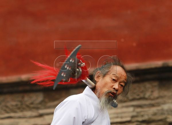 Chinese Wudang Taoist Zeng Yang Hou perform with a sabre staff during a martial arts performance in Carefree Valley of Wudang Mountain in Hubei Province, Central China, 18 October 2010. Wudang Mountain is regarded as the birth place of Wudang Wushu, an important school of Chinese martial arts that effectively combined Taoist theory with kungfu moves. It is noted for its exercise of the internal organs and breathing techniques to develop 'Qi' (internal energy or air flowing through living beings), and its va