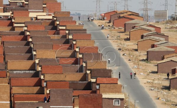 People walk in the street of the newly build government subsidized RDP houses on the East Bank of Alexandra Township, Johannesburg, South Africa, 21 October 2010. EPA/KIM LUDBROOK
