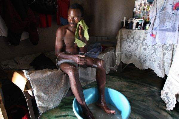 A picture dated 26 November 2009 shows 28-year-old Mfanzile Dlamini (R) bathing in a bowl as his 24-year-old wife Zanele (unseen) prepares food at their home in Mkhulamini, some 40km east of Mbabane, Swaziland. Mfanzile Dlamini died in June 2010 due to the disease. First December is marked annually as World AIDS Day. EPA/JON HRUSA