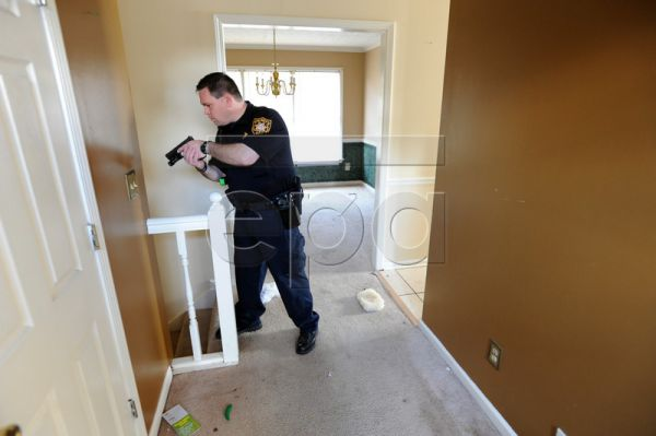 Deputy Alan Shippey with the Gwinnett County Sheriff's Office civil court division carefully checks a property for occupants while serving a foreclosure eviction notice in Lawrenceville, Georgia, USA, 25 February 2011. The Gwinnett County Sheriff's Office has a backlog of at least four weeks of foreclosures and evictions notices that a team of deputies work on every weekday. Gwinnett County leads the metro Atlanta area in foreclosure notices, according to Equity Depot, a real estate data tracking company. G