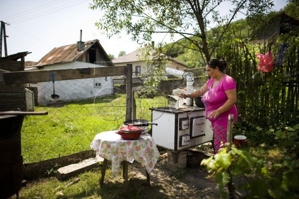 A local woman prepares food for visitors to the Festival of the Dragon, a celebration of Roma art, painting, music and dancing, he​ld for the second time this year in Bodvalenke, some 240 kms northeast of Budapest, Hungary, 09 July 2011. The village is known for the frescoes decor​ating the walls of many of its houses. EPA/ATTILA BALAZS
