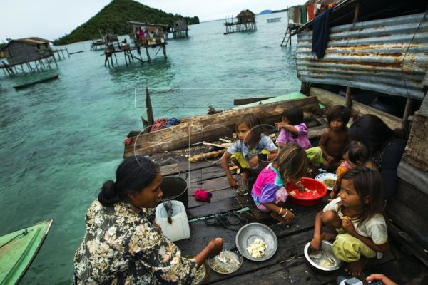 A family of the Bajau Laut ethnic group have a meal at their stilt house just off Bodgaya Island in the Celebes Sea, near Semporna, east coast of Sabah state, Borneo, Malaysia, 30 June 2011. The Bajau, or Bajaw, are an indigenous ethnic group of Maritime Southeast Asia. Due to escalated conflicts in their native Sulu Archipelago, and discrimination suffered by Muslim groups in the Philippines with regards to education and employment, most of the Bajau have migrated to neighboring Malaysia over the course of
