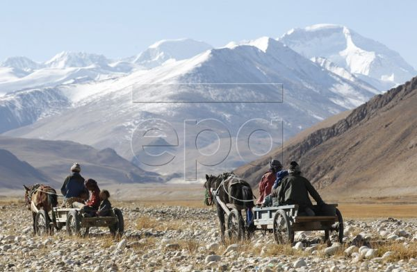 Tibetan nomads on horse-drawn carts travel towards the Himalayan ranges on the road to the base camp of the earth's highest peak o​f Mt Everest, in the Tibet Autonomous Region, the People's Republic of China, 13 October 2011. Tibet is a vast land of harsh, arid, brown plateaus and​ majestic mountain ranges. Living in the thin air of this high altitude desert are many nomads. Religion is an integral part of life for Tibetans, and​ most partake in religious pilgrimages of hundreds of kilometers to visit the r