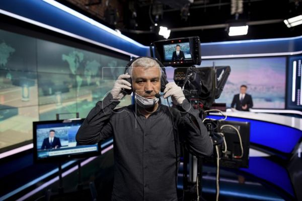 Camera operator Giannis Mentzos, 49, wearing a protective face mask and gloves poses for a picture as he films a news anchor during the lockdown of the coronavirus disease (COVID-19) outbreak, at the headquarters of state broadcaster ERT in Athens, Greece, 25 April 2020. During the coronavirus disease (COVID-19) outbreak, we acquired new habits, we even distanced ourselves from our loved ones, we wore masks, we filled our pockets with antiseptic wipes and sprays and most importantly, we learned to 'Stay hom