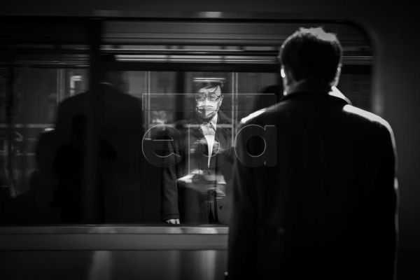 A commuter wearing a face mask is reflected in a train window as it arrives at the platform of Shibuya train station in Tokyo, Japan, 14 April 2020, a week after the Japanese government declared a state of emergency on parts of Japan including Tokyo and Osaka, in a bid to slow the spread of the coronavirus SARS-CoV-2 which causes the Covid-19 disease.  EPA-EFE/DAI KUROKAWA