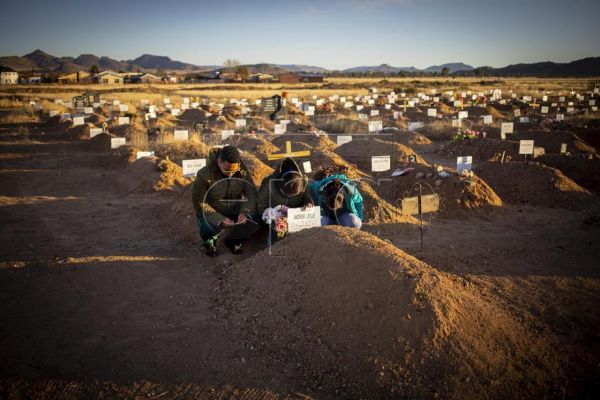Widow Colette Leslie (46) and her two children, Curtley (L) and Adreulishe (R), pray at the graveside of their late father, Captain Andrew Leslie, in Middleburg, South Africa, 14 June 2020. Captain Leslie died with the Covid-19 coronavirus a month earlier and was the first victim of the virus in the town. He was acting station commander of the local police station. Many of the people in the district infected with the coronavirus are front line workers. In the barren expanses of the Karoo (Great dry land) in