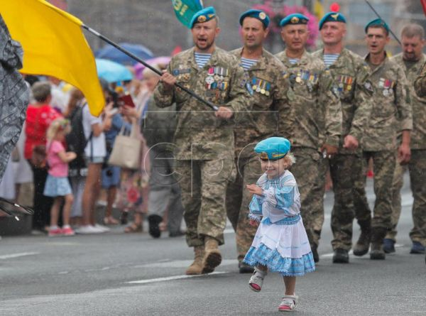 A little Ukrainian girl plays during the march of Ukrainian defenders dedicated to 'Independence Day' celebration in downtown Kiev, Ukrain​e, 24 August 2020. Ukrainians mark the 29th anniversary of Ukraine's independence from the Soviet Union in 1991. EPA-EFE/SERGEY DOLZHENKO