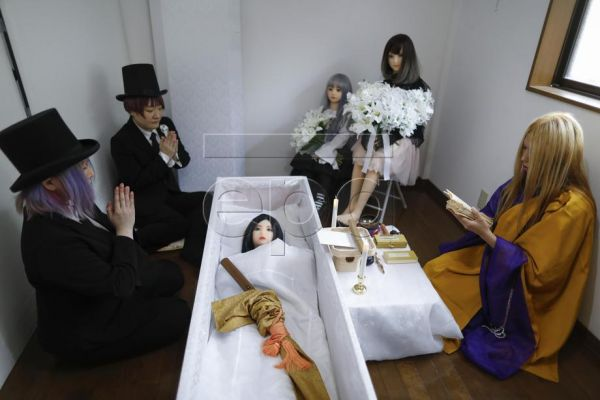 Buddhist monk and an undertaker Lay Kato (R), Leiya Arata (L), and a makeup artist Hiiro (2-L) pray while sex dolls Rinne (3-R) and Sayaka (2-R) as mourners attend a funeral service for a sex doll named Ran (3-L) at a home studio in Osaka, Japan, 26 June 2020. A samurai sword placed on Ran's body is ceremonially given to the dead to protect themselves from evil spirits on their way to the afterlife world. Freelance photographer Leiya Arata provides a range of services at her studio in Osaka, including funer