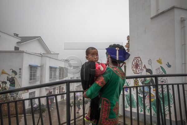 An Yi ethnic minority woman who was relocated from remote areas holds a child as she stands in Xujiashan village during a government-organised media tour, in Ganluo County, China's Sichuan Province, 10 September 2020. Over the past four decades, China says it has lifted more than 800 million people out of poverty, a phenomenon that has been described as 'unmatched in human history' by politicians such as former World Bank President Jim Yong Kim. Over the past five years, 70 million people have been the bene