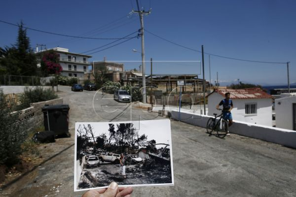 The photojournalist holds a picture he has taken a year ago showing a woman walking in front of burned cars following the deadly forest fire in Mati on 24 July 2018, as a man walks with his bicycle on a street at the same point a year later, in the coastal village of Mati, northeast of Athens, Greece, 19 July 2019. One year after the deadly fire, Mati remains a ghost village. Many of the people who once lived or made their summer holidays have left it permanently. The remains of the houses that still stand,