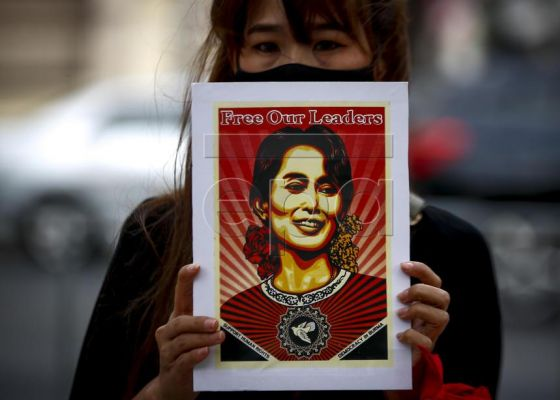 A Myanmar demonstrator wearing a protective face mask holds a sign with the image of Myanmar democracy icon Aung San Suu Kyi during a protest against the Myanmar military coup, outside the United Nations building in Bangkok, Thailand, 17 February 2021. Myanmar nationals living in Thailand continue to rally against the military coup, and in support of their democratic leader Aung San Suu Kyi and other top political leaders who were detained in a raid during a military coup, after tensions rose between the ci